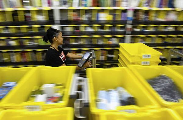 An employee pushes a cart of bins through the sorting area at the Amazon.com distribution center in Phoenix on cyber Monday.