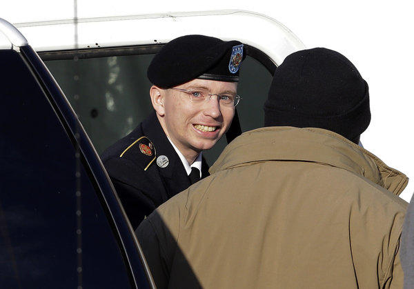 Army Pfc. Bradley Manning, center, steps out of a security vehicle as he is escorted into a courthouse in Ft. Meade, Md., for a pretrial hearing.