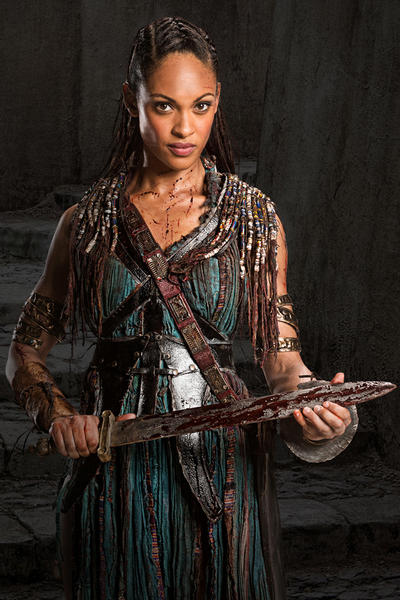 NAEVIA <br>Cynthia Addai-Robinson <br>A former body slave to Lucretia, Naevia was banished from the ludus after engaging in a love affair with Crixus. Her punishment was severe; she was sent to the salt mines where she endured horrific conditions and violent assaults from both Roman soldiers and other slaves. When Crixus learned of her fate, he launched a rescue. The mission was a success but their reunion was short-lived, as Crixus was captured by the Romans. Since Crixus escaped and reunited with Naevia, they share a bond unlike any other. Naevia, deeply wounded from her past, is trained as a fighter and now uses these skills to satiate her thirst for revenge. She is now a fierce warrior and fights alongside her love.