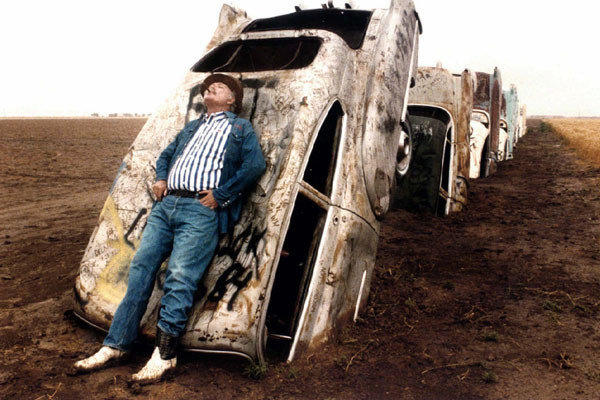 In this June 1984 photo, artist Stanley Marsh 3 poses with one of the 10 vehicles in his Cadillac Ranch installation near Amarillo, Texas.