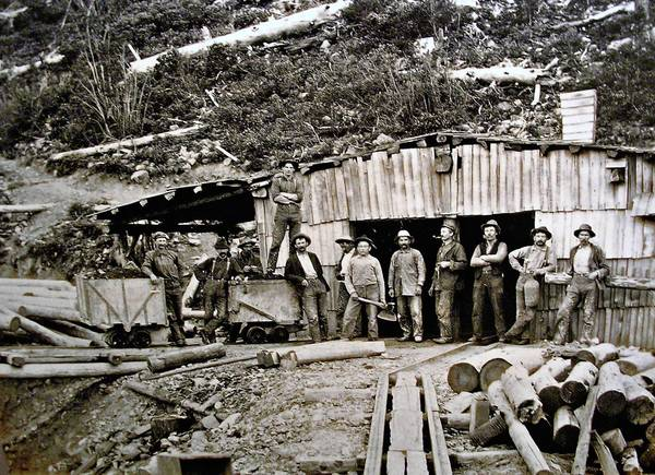 Miners hang out in front of the Dewey mine in an old sepia-toned photograph on display at the Siskiyou County Museum.