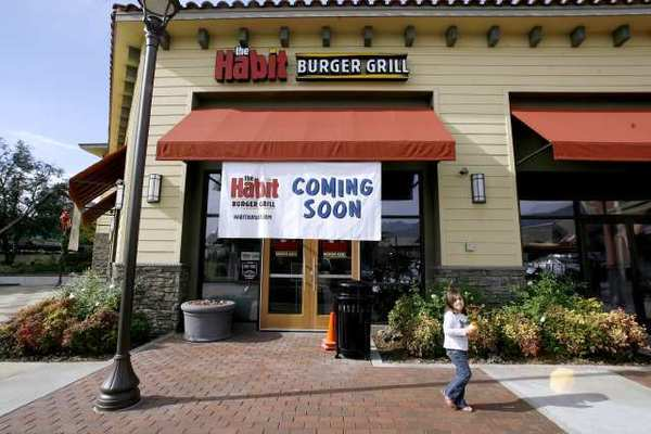 A young girl walks past the soon-to-open Habit Burger Grill at the Town Center in La Canada Flintridge.