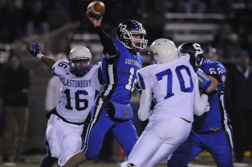 Southington's Stephen Barmore, 12, makes a pass as Glastonbury's Joshua Hill, 16, and Jordan Butler, 70 apply preasure. Blocking for Southington is Travis Clark, 68. Glastonbury High School beat Southington High School in a quarterfinal game in the Class LL HS football playoffs at Southington by a score of 23 to 14.