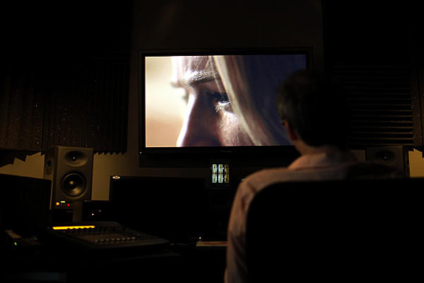 "Writer and director Nicholas McCarthy watches his movie ""The Pact,"" with lead actress Caity Lotz on screen, one last time at Secret Headquarters, a postproduction company for film and TV, in Culver City. Following the viewing, the film was shipped to Park City, Ut., for it's premier at the Sundance Film Festival."