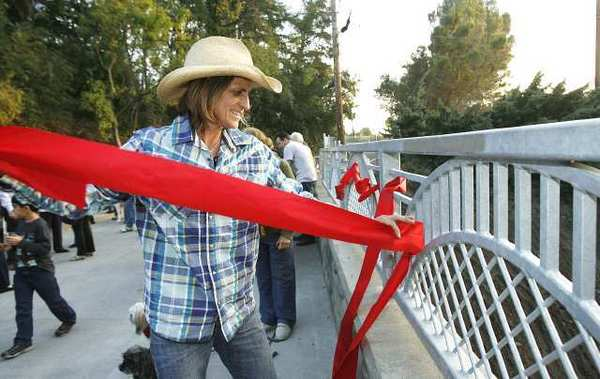Julie Thurston, who lives near the Jessen Bridge, threads the red ribbon that was cut during the ribbon-cutting ceremony for the bridge into the safety rail as a decoration.