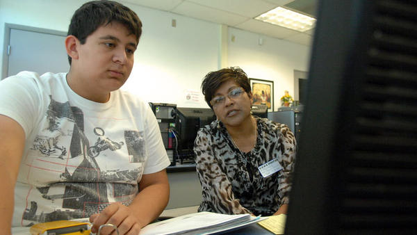 FROM LEFT: Roberto Ramirez, 17, is helped by student support specialist Francisca Lopez apply to universities offering nursing majors during college application workshops in the Central Union High School career center in El Centro on Wednesday.