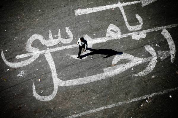"A man walks over graffiti reading ""Morsi Go"" at Tahrir Square in Cairo on Sunday."