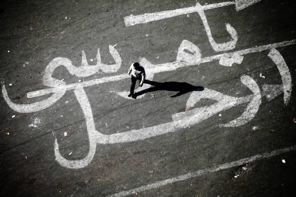 "A man walks over graffiti reading ""Morsi Go"" at Tahrir Square in Cairo on Sunday."