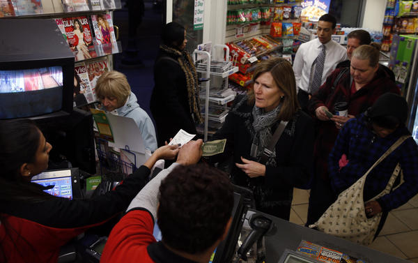 People line up to buy Powerball tickets at a 7-Eleven at Washington and Wells during the evening rush hour Wednesday.