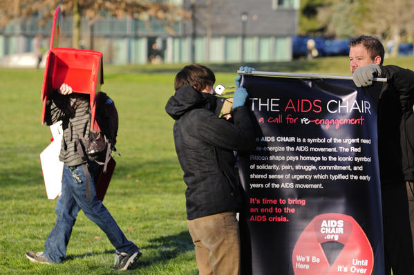 Matthew Blocker-Glynn, director of community service at the University of Hartford and adviser to Spectrum, the student LGBT campus organization, sets up an informative banner in front of the AIDS Chair display in the main quad. Students and staff set up 88 chairs outside the Gengras Student Union on Thursday morning to recognize World AIDS Day on Dec. 1.