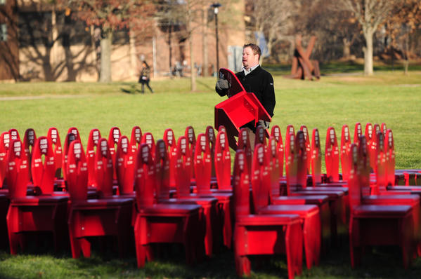 Matthew Blocker-Glynn, director of community service at the University of Hartford and adviser to Spectrum, the student LGBT campus organization, sets up AIDS Chairs in the main quad. Students and staff set up 88 chairs outside the Gengras Student Union on Thursday morning to recognize World AIDS Day on Dec. 1.