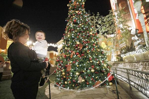 Anna Orme and her grandson Conner Bohannon enjoy the Christmas tree and decorations at the Bella Terra shopping center in Huntington Beach.