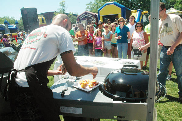 A crowd gathers to watch a grilling demonstration at this year's Up North Fourth event in Charlevoix's East Park. Downtown development authority officials have said the Up North Fourth event will not be returning in 2013.