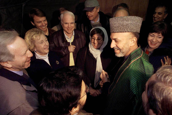 Afghanistan's interim leader Hamid Karzai (R) meets with U.S. Senators at the Bagram airbase some 50 kilometers (30 miles) from Kabul, January 7, 2002. Nine U.S. senators arrived at Bagram and met with Karzai and several members of the new interim administration. Shown are Senator L-R, Joseph Lieberman (D-CT), Jean Carnahan, (D-MO), John Edwards (D-NC), John McCain (R-AZ), Fred Thompson (R-TN), and Susan Collins (R-ME). Afghan Women's Affairs Minister Sima Samar is at center in glasses.