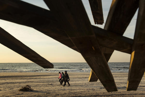 A group of people walk on the beach past sections of boardwalk damaged by the storm surge of superstorm Sandy in Long Beach, New York