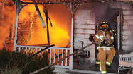 Firefighters from three departments spent hours battling a three-alarm fire on College Street that burned two homes to the ground and damaged a third.