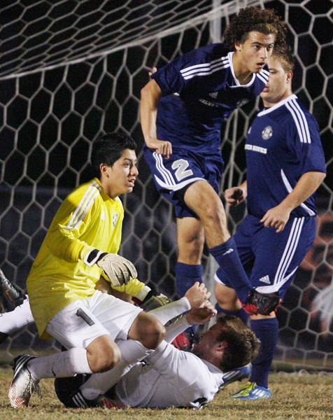 Lake Howell's Arick Gonzalez (2) and goalkeeper Danny Herreria (lower left) collide with others in front of the goal during the Lake Howell at Seminole High School boys soccer game in Sanford on Tuesday, November 27, 2012.