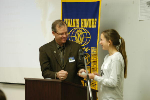 Katelyn Skornia, pictured here receiving a check from Boyne City Kiwanis president Scott Mackenzie, was named the silver prize winner in the Kiwanis Club's annual essay contest. She donated the $200 prize to Trailing for Triumph, a local charity that raises money for breast cancer patients.