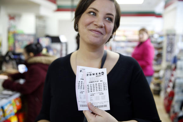 Tara Brinkman, 35, shows off the Powerball tickets she bought as part of the office pool at a 7-Eleven store at East Wacker Drive and North Wabash Avenue in Chicago on Wednesday. The Powerball is at $550 million.