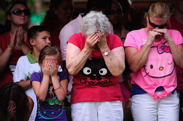"People mourn during a memorial for the 12 victims killed in a theater shooting in Aurora, Colo., in July during a midnight screening of ""The Dark Knight Rises."""