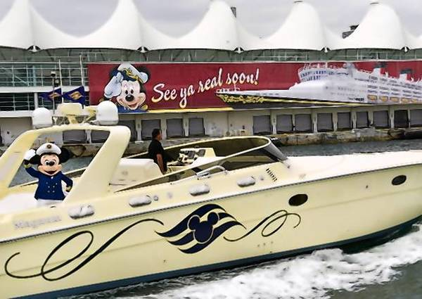 "Mickey Mouse zips across Biscayne Bay in a powerboat this week (Wednesday) with a banner, ""See ya real soon!"" that promotes the start of cruises out of Miami on Dec. 23 by the Disney Wonder."