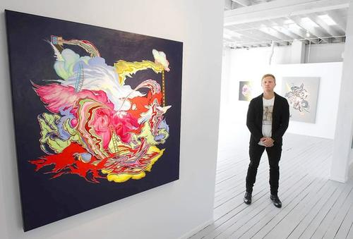 Gallery director Carl Smith stands with a piece by artist Mike Parillo, left, in the new CES Contemporary in downtown Laguna.