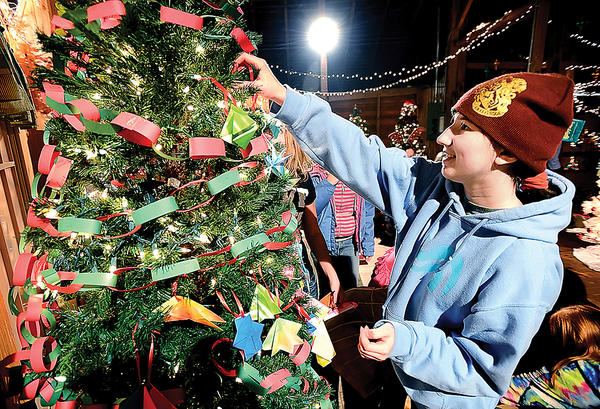 Homeschooler Elizabeth Jacobs, 14, decorates the Potomac Home Learning Circle tree Wednesday at Springfield Barn. The tree is among those featured at Charlie Brown Christmas - Reindeer in the Rafters beginning Saturday at the Williamsport barn.