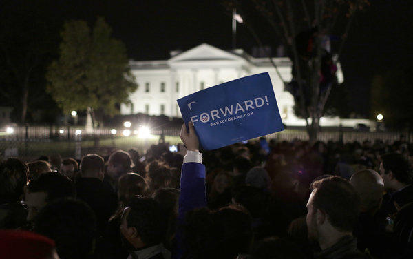"A Democratic supporter holds a ""Forward"" sign as people gather to celebrate President Obama's re-election in front of the White House in Washington."