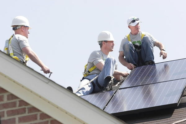 Wearing a hard hat, Gov. Martin O'Malley, center, joins workers for Astrum Solar on Earth Day 2010 as they put photovoltaic panels on a roof in Howard County.