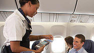 A United flight attendant swipes a credit card for a passenger's purchase.