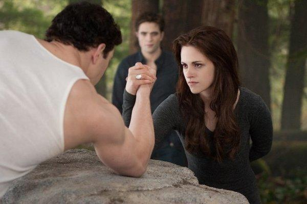 "Edward (Robert Pattinson) watches Bella (Kristen Stewart) arm-wrestle Emmett (Kellan Lutz) in ""The Twilight Saga: Breaking Dawn -- Part 2."""