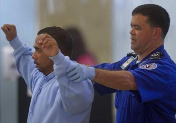 A travelers gets a pat-down search at John Wayne Airport.