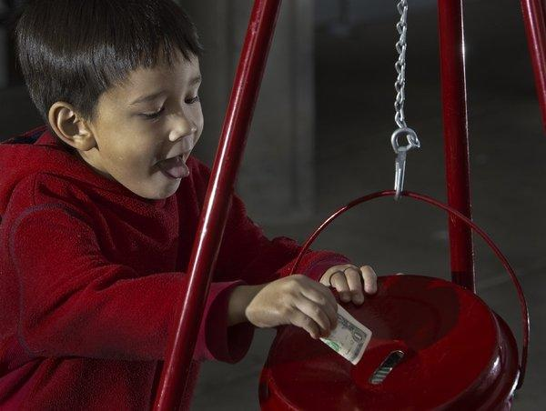 A young boy stuffs a donation into a Salvation Army kettle outside a grocery store in Virginia on Saturday. Unlike the charities that hire commercial fundraising companies, the Salvation Army gets to keep all the money its staff and volunteers collect in its kettles.
