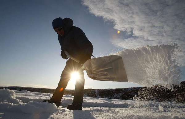 A researcher shovels snow from the surface of a frozen tundra lake in search of frozen bubbles that indicate a seep of methane gas, which is created when microbes digest organic material contained in permafrost.