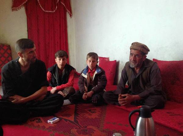 Jan Agha, right, is shown with his nephew, left, his son and his grandson in the Afghan village of Naqi Khail, as they mourn the death of Agha's son Zabiulla.