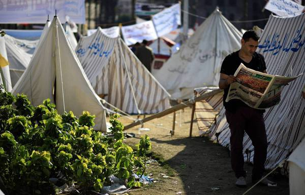 An Egyptian protester reads a newspaper next to tents pitched in Cairo's Tahrir Square. Supporters of President Mohamed Morsi plan to hold a major rally this weekend.