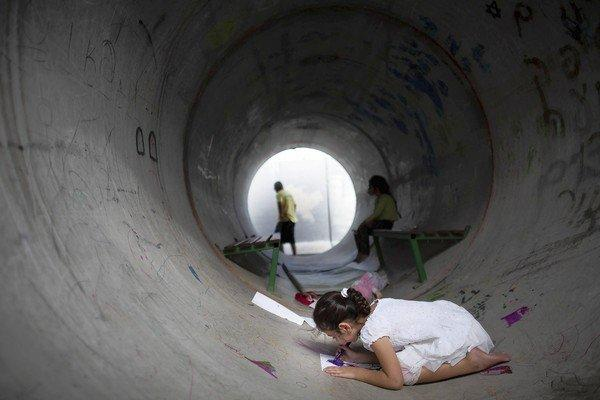 An Israeli child in Nitzan draws inside a concrete pipe used as a bomb shelter during the recent conflict with Hamas. Shelter life was one of the topics that provided fodder for Israeli -- and Palestinian -- humor during the strife.