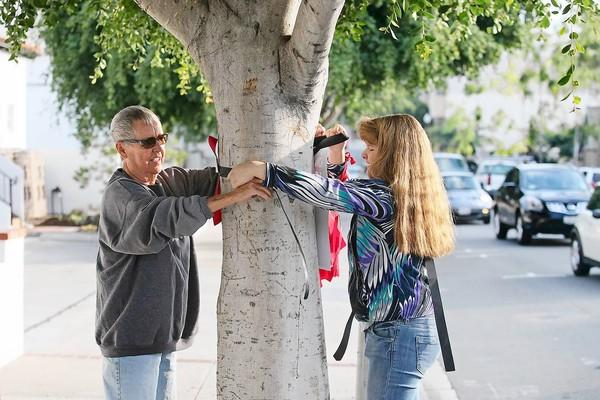 Julie Phillips, left, and Veronica Hinmon, 16, attach red ribbons with names of those affected by HIV and AIDS to trees along Forest Avenue in Laguna Beach on Tuesday.