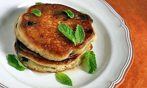 Olive oil pancakes studded with Spanish chocolate and garnished with lemon honey and fresh mint.