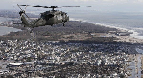 An Air National Guard helicopter flies above the Breezy Point neighborhood in New York where more than 100 homes, lower right, were burned to the ground during superstorm Sandy.
