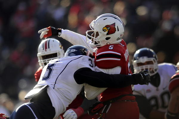Huskies linebacker Sio Moore puts the hit on Louisville Cardinals quarterback Teddy Bridgewater during the second half of a three-overtime UConn victory in Louisville last Saturday.