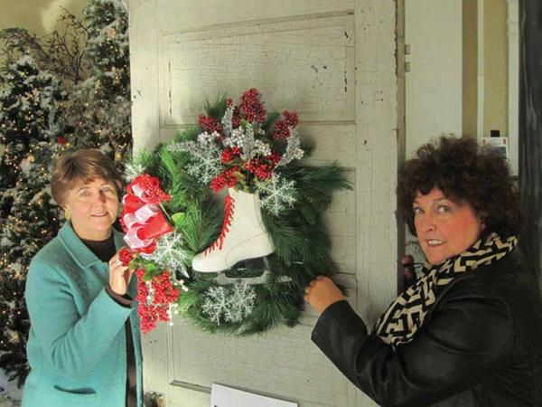 Donna Sperow, left, and Harriet Johnson showing off one of the wreaths that will be auctioned off Dec. 6 for Main Street Martinsburg's annual Home for the Holidays Christmas season celebration.