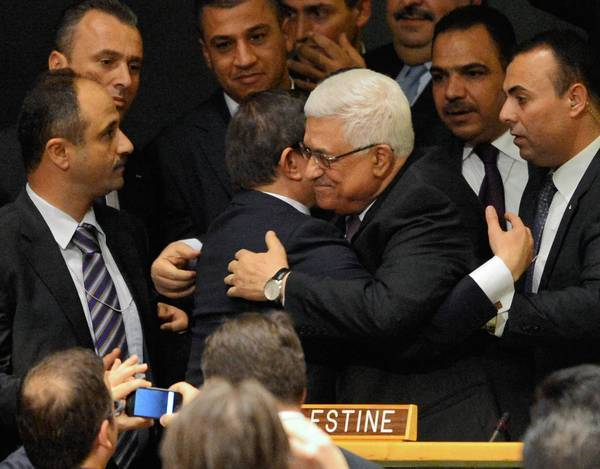 "Palestinian Authority President Mahmoud Abbas, right, receives a hug from Ahmet Davutoglu, Turkey's foreign minister, after the U.N. General Assembly voted to upgrade the Palestinian status to ""nonmember observer state."""