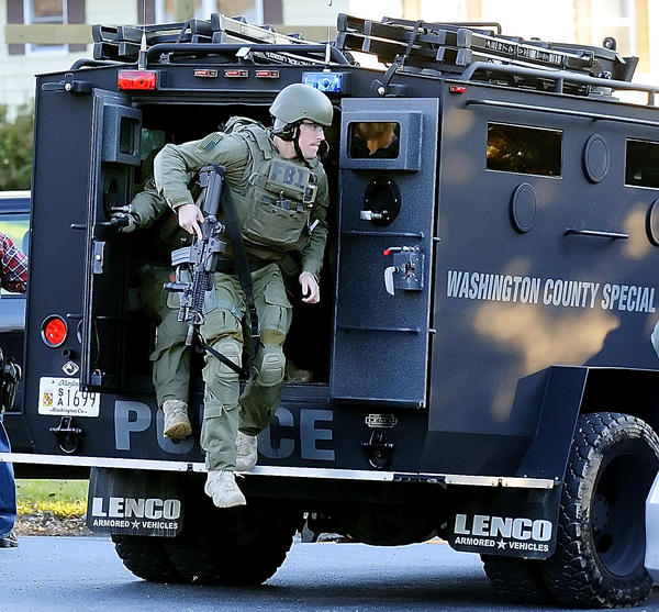 Agents from the FBI SWAT Team from Baltimore exit the Washington County Special Response Team's armored vehicle at the intersection of Burnside Bridge Road and Mills Road Thursday afternoon.