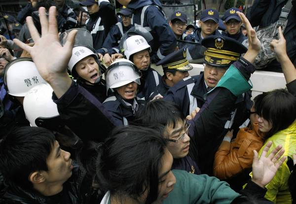 Demonstrators protesting the proposed sale of Next Media group in Taiwan scuffle with police in Taipei, the capital.