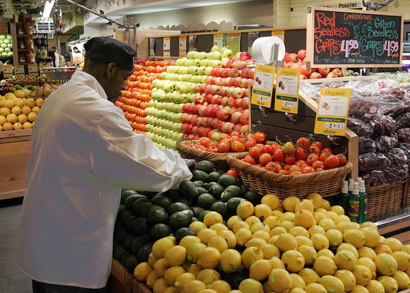 A grocer arranges avocados and lemons in the produce section at Whole Foods.