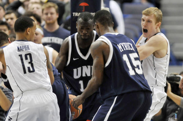 UConn's Shabazz Napier and Niels Giffey, right, fight for a rebound against, from left, Chris Pelcher, Patrick Konan and Ferg Myrick of New Hampshire.