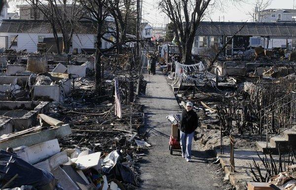 Louise McCarthy carts belongings from her flood-damaged home as she passes charred ruins in the Breezy Point section of New York's Queens borough.