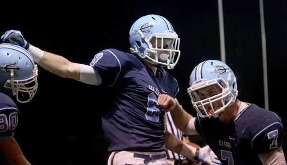 Corona del Mar High quarterback Cayman Carter (7) and Troy Reese (center) hope to be celebrating on Saturday too.