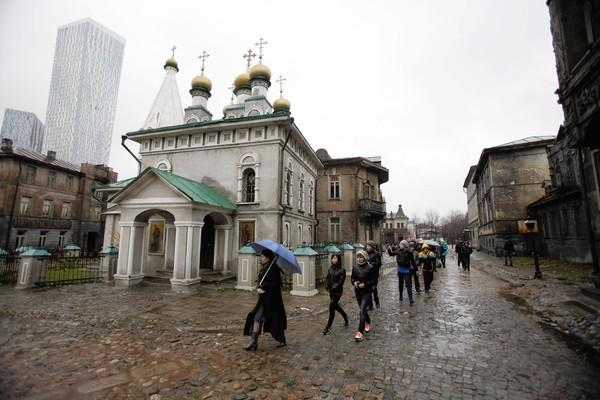 Schoolchildren walk past the old Moscow movie-set scenery as part of the tour of the Mosfilm Studios in downtown Moscow.